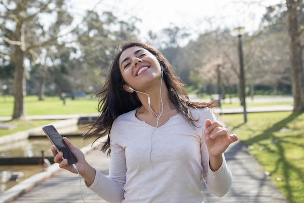 Muchacha alegre del estudiante en los auriculares que sostienen smartphone y el baile