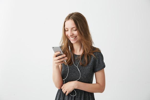 Muchacha alegre feliz que sonríe mirando la pantalla del teléfono que escucha la transmisión de música.