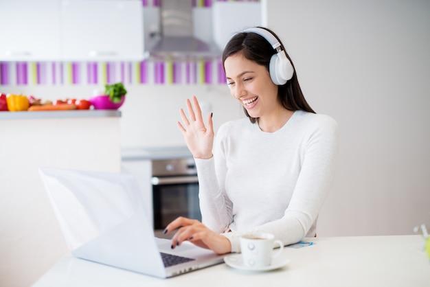 Muchacha alegre hermosa joven con los auriculares en la mirada de la computadora portátil que bebe el café y que ríe mientras que se sienta en la tabla de cocina.