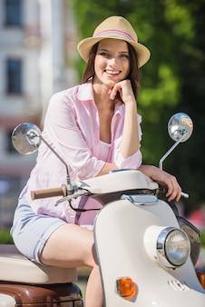 Muchacha alegre joven que se sienta en la vespa en ciudad europea.