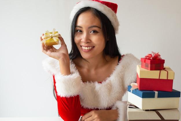 Muchacha alegre de la navidad que muestra la pequeña caja de regalo