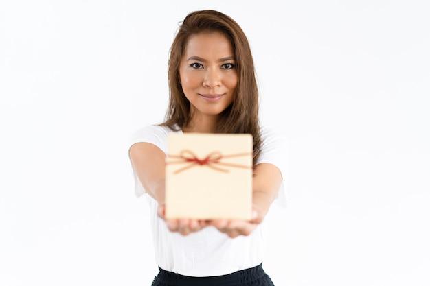 Muchacha alegre positiva que da el regalo