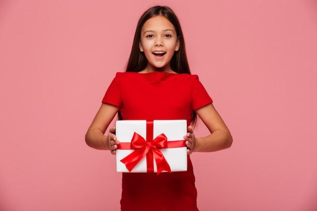 Muchacha alegre que muestra el regalo y la sonrisa aislada sobre rosa