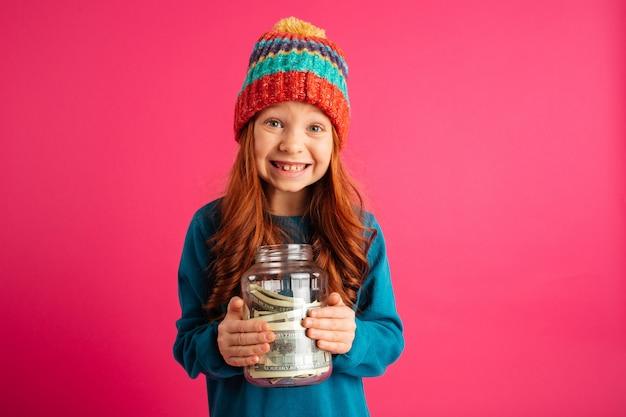 Muchacha alegre que sostiene la caja de dinero y que sonríe a la cámara aislada