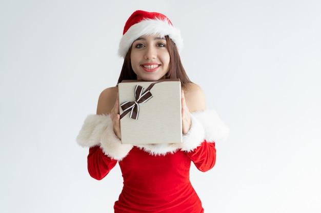Muchacha alegre en el sombrero de papá noel emocionado sobre el regalo de navidad