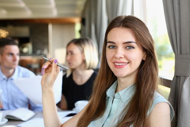La muchacha alegre sonriente hermosa en el lugar de trabajo mira in camera con el grupo de los colegas. trabajador de cuello blanco en el espacio de trabajo, oferta de trabajo, visita del cliente, concepto de tren profesional