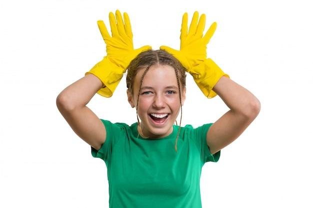 Muchacha alegre sonriente joven en guantes protectores de goma amarillos