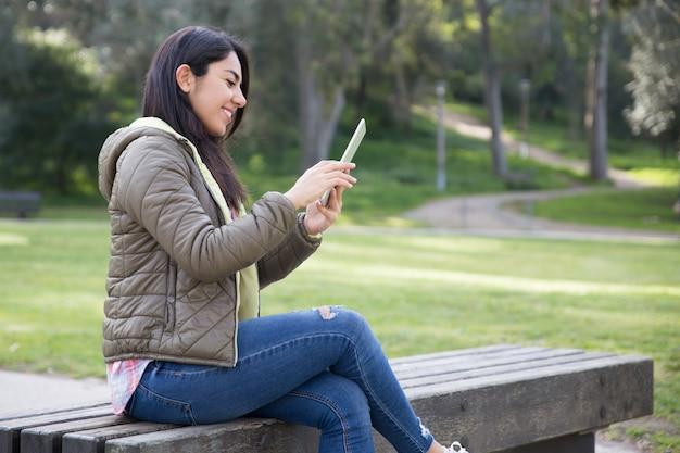 Muchacha alegre sonriente que disfruta de la conexión inalámbrica en parque de la ciudad