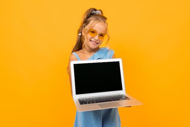 La muchacha alegre en vestido sonríe con su computadora portátil aislada en amarillo y naranja
