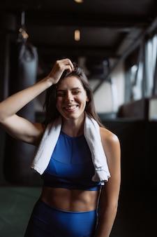 Muchacha apta sonriente que sostiene la toalla y que descansa en gimnasio.