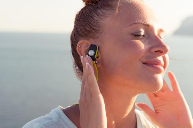 Muchacha de la aptitud con los auriculares sin hilos