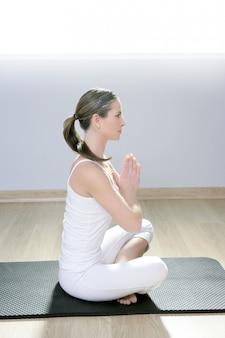 Muchacha de la aptitud de la mujer de la yoga en la meditación blanca en el gimnasio