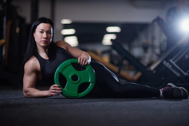 Muchacha de la aptitud que descansa en el gimnasio, sosteniendo una cáscara para entrenar