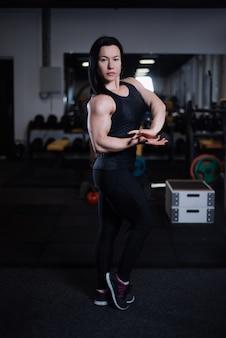 Muchacha de la aptitud que descansa y que muestra apagado sus músculos en el gimnasio.