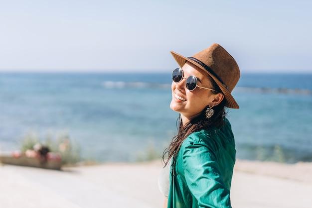 Muchacha asiática de la cacerola linda en sombrero y gafas de sol en pareo verde que camina en la playa.