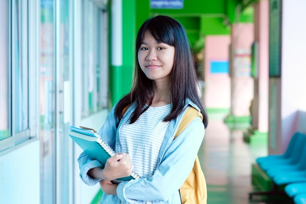 La muchacha asiática del estudiante que sostiene los libros y lleva el bolso de escuela mientras que camina en fondo de la escuela