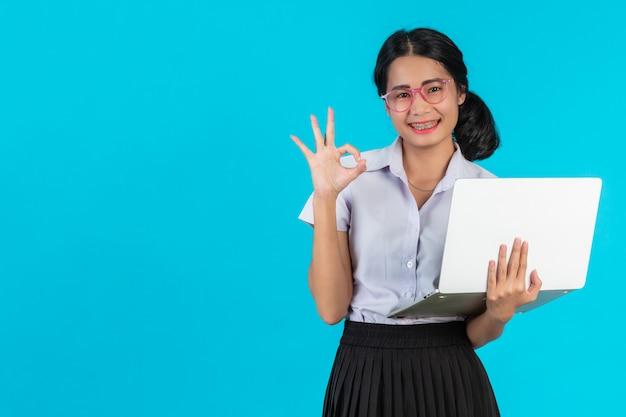 Una muchacha asiática del estudiante que sostiene su cuaderno en un azul.
