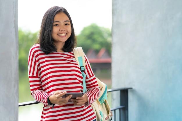 Muchacha asiática del estudiante con una tableta digital en el parque en un día de verano soleado