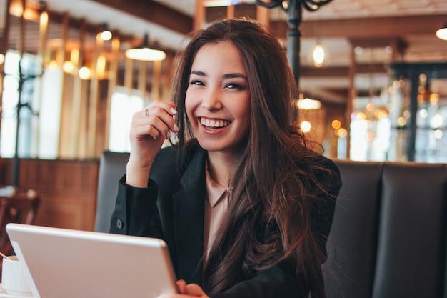 Muchacha asiática feliz morena encantadora hermosa con la tableta en la tabla en café