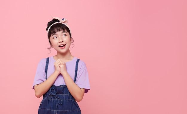 Muchacha asiática feliz del niño aislada en la pared rosada del espacio de la copia.