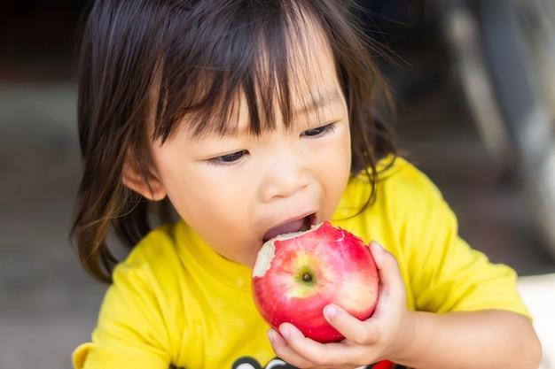 Muchacha asiática feliz del niño que come y que muerde una manzana roja.