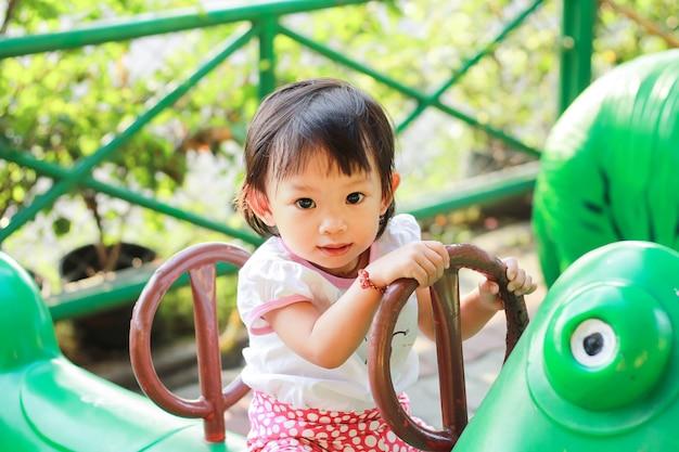 Muchacha asiática feliz del niño que juega los juguetes en el patio. ella sonriendo.