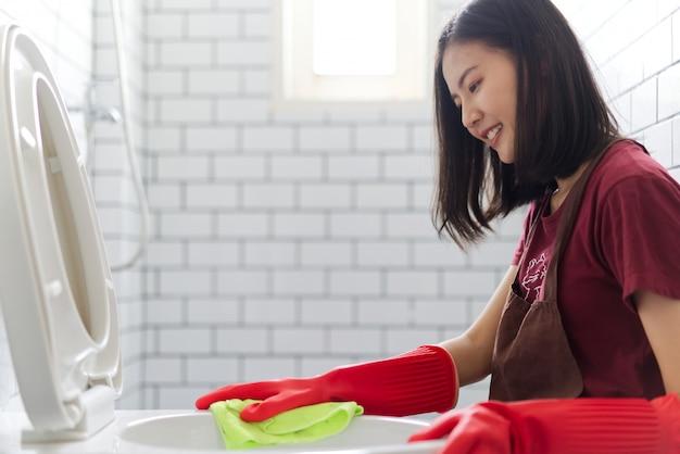 La muchacha asiática con los guantes de goma rojos está limpiando la taza del inodoro.