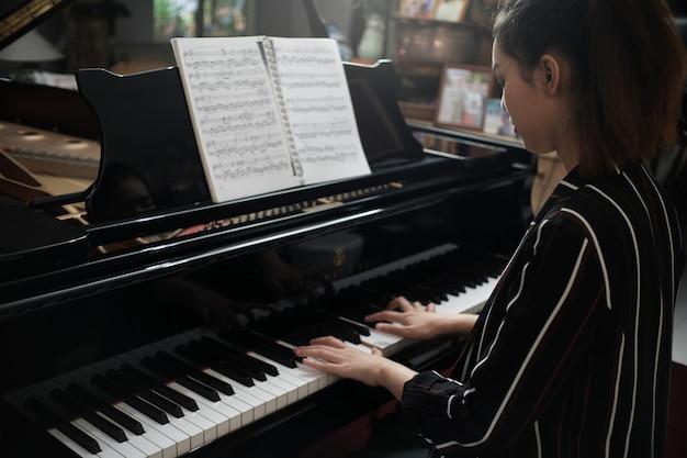 La muchacha asiática hermosa aprende tocar el piano.