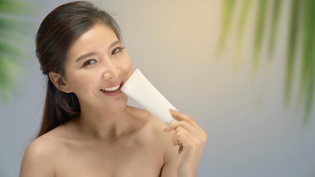 Muchacha asiática hermosa feliz con la piel fresca con el fondo de la luz del sol.
