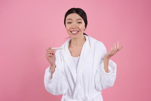 La muchacha asiática hermosa está presentando con la prueba de embarazo.