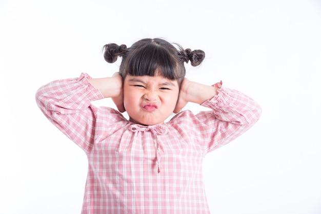 Muchacha asiática infeliz que se cierra los oídos por las manos aisladas sobre el fondo blanco