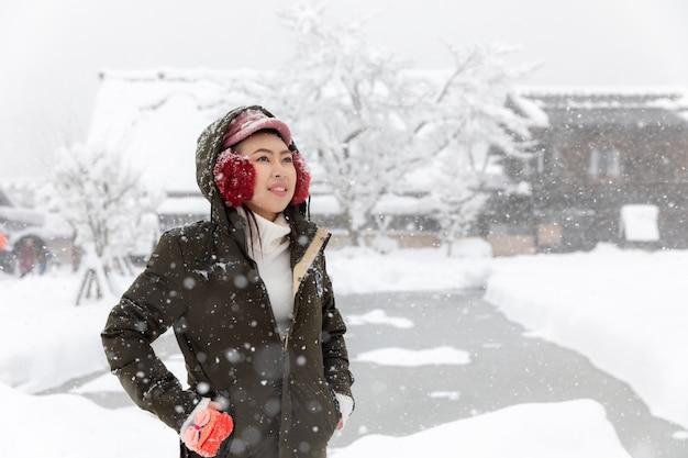 Muchacha asiática joven de la mujer en la estación de la nieve del invierno