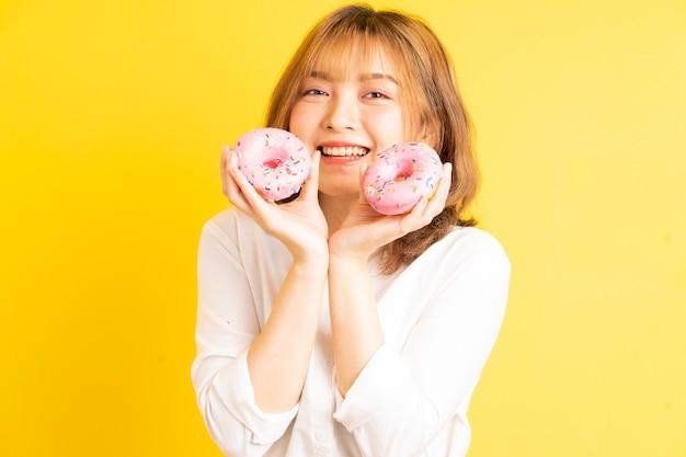 Muchacha asiática joven que sostiene el buñuelo con expresión alegre en el fondo