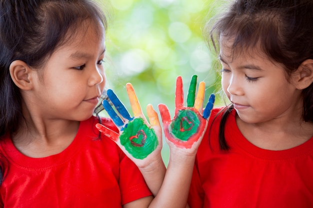 Muchacha asiática linda de dos niños con las manos pintadas que sonríen y que juegan junto