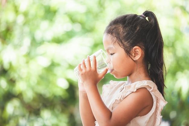 Muchacha asiática linda del niño que bebe el agua dulce del vidrio