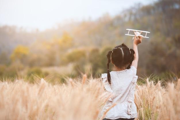 Muchacha asiática linda del niño que corre y que juega con el aeroplano de madera del juguete en el campo de la cebada