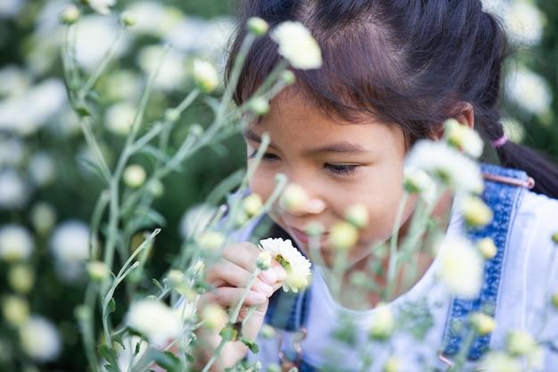 Muchacha asiática linda del niño que huele la flor hermosa en el campo de flor con felicidad