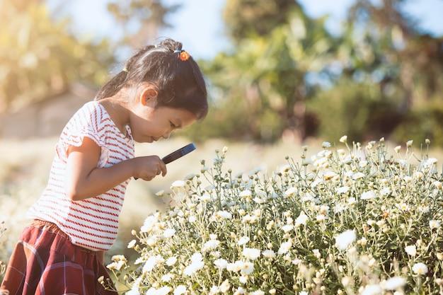 Muchacha asiática linda del niño que mira la flor hermosa a través de una lupa en el campo de flor