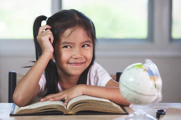 Muchacha asiática linda del niño que piensa al hacer la tarea en su sitio