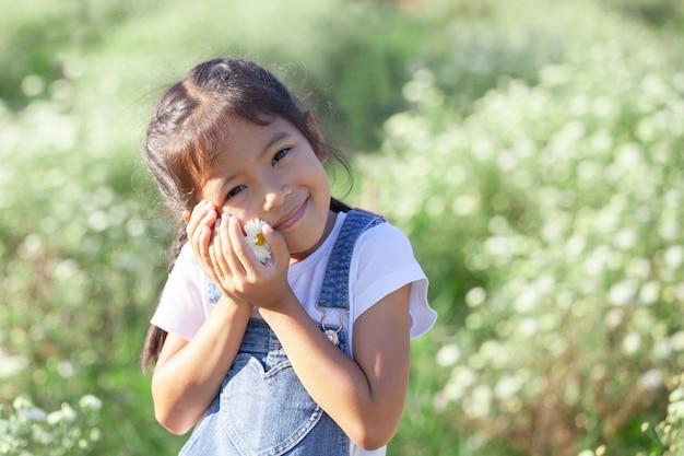 Muchacha asiática linda del niño que sonríe y que sostiene la pequeña flor disponible en el campo de flor