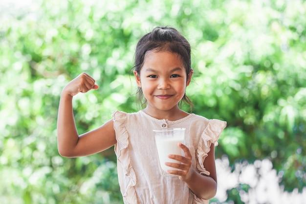 La muchacha asiática linda del niño que sostiene el vidrio de leche y hace gesto fuerte