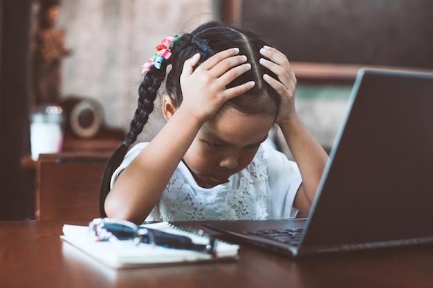 Muchacha asiática linda del niño que tiene tensión y que hace la cara preocupante delante del ordenador portátil