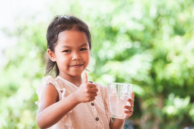 La muchacha asiática linda del niño tiene gusto de beber el agua y de sostener el vidrio de agua dulce