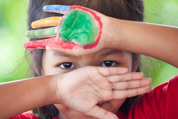La muchacha asiática linda del pequeño niño con las manos pintadas cerró su cara y mostrando solamente sus ojos