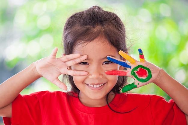 Muchacha asiática linda del pequeño niño con las manos pintadas que sonríe con la diversión y la felicidad