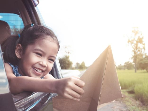 Muchacha asiática linda del pequeño niño que se divierte para jugar con el aeroplano de papel del juguete de la ventana de coche