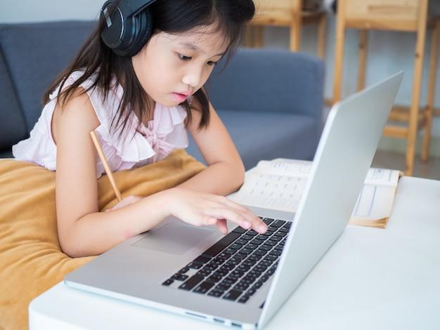 La muchacha asiática linda usa la computadora portátil para estudiar la lección en línea durante la cuarentena casera.