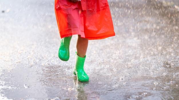 La muchacha asiática lleva la bota verde. ella está bajo la lluvia.