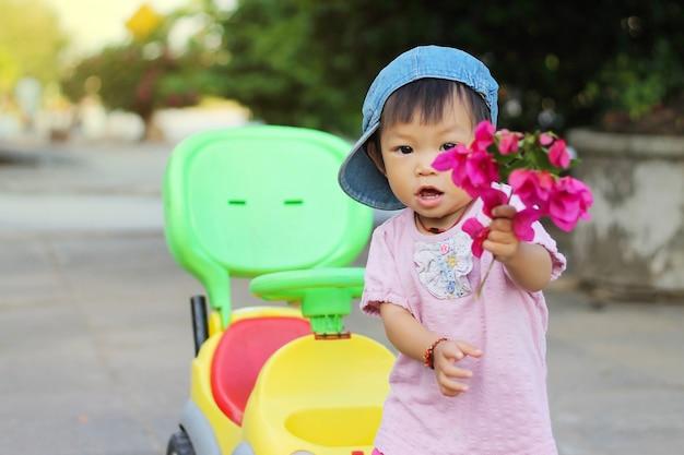 Muchacha asiática del niño del bebé que sostiene las flores rosadas en su mano y que juega un juguete del coche en el patio.