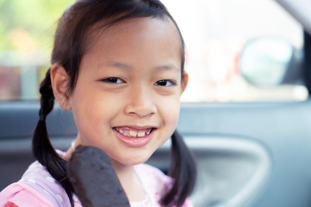 Muchacha asiática del niño que se siente feliz con la consumición de la barra de helado de chocolate en coche